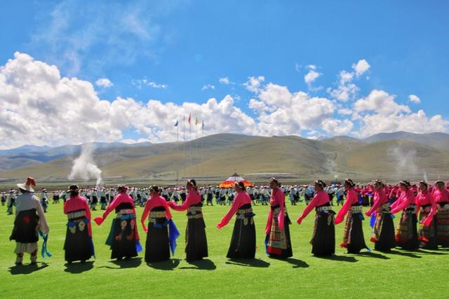 The dressed-up Tibetans are dancing on the grassland