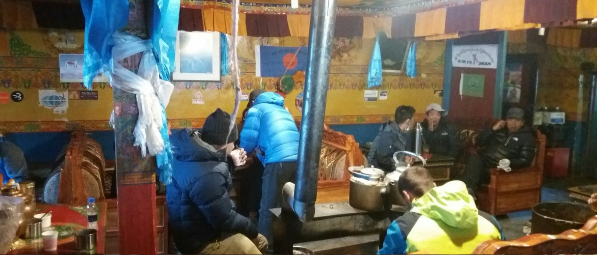 Travelers are talking and inquire about the info at the lobby of Rongbuk Hotel