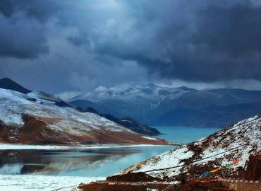 Lake Yamdrok is surrounded by snow-capped mountains in February.