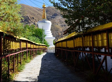 An alley of prayer wheels leading up to a pagoda.